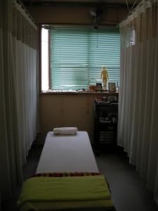 治療室のベッド1台と奥の出窓の写真