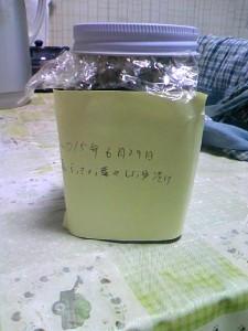 ラベルの貼ったガラス瓶に島らっきょの葉を醤油漬け