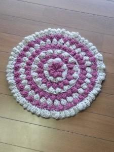 ベージュと赤が同心円状になった手編みの座布団